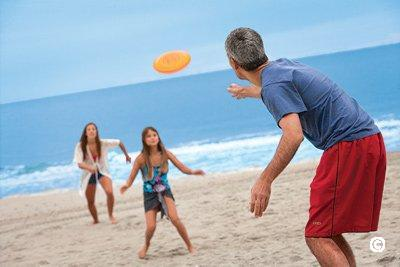 family playing frisbee on the beach